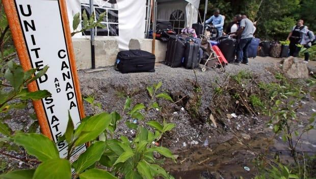 Migrants stack their luggage outside a makeshift police station after crossing illegally into Canada at the end of Roxham Road in Champlain, N.Y. on Aug. 7, 2017. A CBSA report says the pandemic is expected to drive a surge in immigration fraud and human smuggling. (Charles Krupa/The Associated Press - image credit)