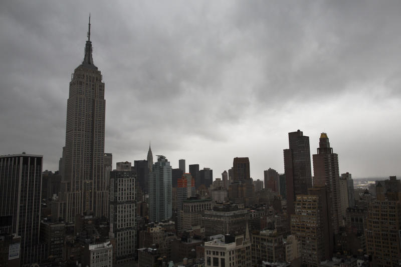 Storm clouds loom over the Empire State Building and Manhattan skyline, Monday, Oct. 29, 2012, in New York. Hurricane Sandy continued on its path Monday, forcing the shutdown of mass transit, schools and financial markets, sending coastal residents fleeing, and threatening a dangerous mix of high winds and soaking rain.  (AP Photo/ John Minchillo)