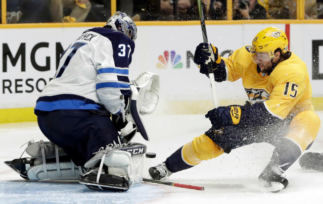 Winnipeg Jets goalie Connor Hellebuyck (37) blocks a shot from Nashville Predators right wing Craig Smith (15) during the second period in Game 1 of an NHL hockey second-round playoff series Friday, April 27, 2018, in Nashville, Tenn. (AP Photo/Mark Humphrey)