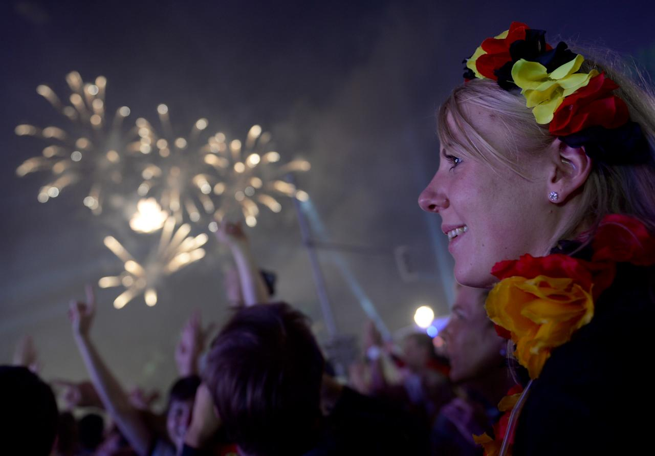 CORRECTS DATE -Fireworks illuminate the sky as German fans celebrate their team after  Germany  won  against Argentina  by 1-0 at the soccer World Cup final in Rio de Janeiro, Brazil,  at a public viewing area called 'Fan Mile'  in Berlin,  early Monday July 14, 2014. (AP Photo/dpa,.Britta Pedersen)