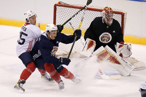 Florida Panthers goaltender Philippe Desrosiers, right, defends the goal as defenseman Brady Keeper (25) and Mason Marchment, center, go for the goal during NHL hockey training camp, Tuesday, Jan. 5, 2021, in Sunrise, Fla. (AP Photo/Lynne Sladky)