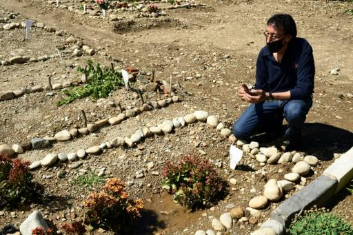 Morocco's Mustapha Moulay prays before his wife's simple grave
