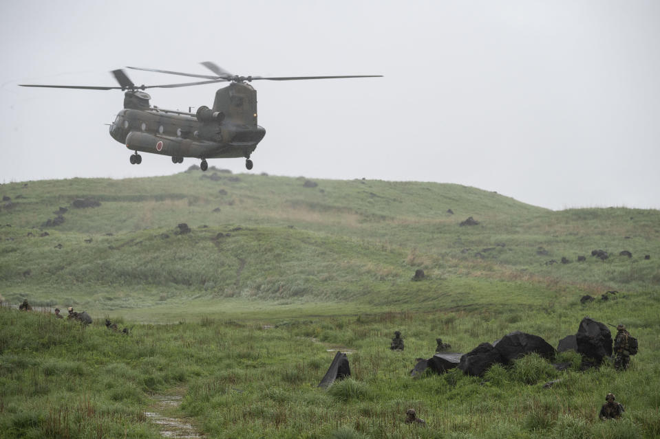 A Chinook helicopter flies over a field during a joint military drill between Japan Self-Defense Force, French army and U.S. Marines, at the Kirishima exercise area in Ebino, Miyazaki prefecture, southern Japan Saturday, May 15, 2021. (Charly Triballeau/Pool Photo via AP)