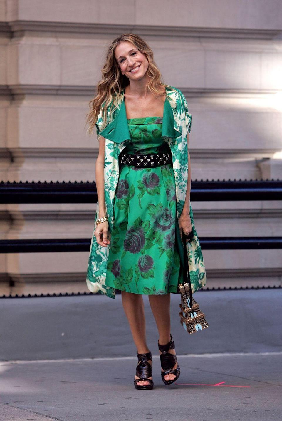 <p>More than three years after we left Carrie Bradshaw in Paris, Sarah Jessica Parker stepped back into her Manolo Blahniks to reprise her famous role. The film's opening outfit—a now-iconic contrasting mix of a green printed dress and jacket, topped off with a black spiked belt—did Bradshaw's unique style justice. </p>