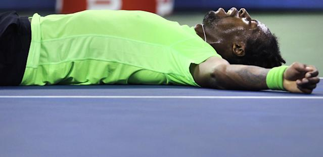 Gael Monfils, of France, lies on the court after taking a tumble on a return against Roger Federer, of Switzerland, during the quarterfinals of the U.S. Open tennis tournament, Thursday, Sept. 4, 2014, in New York. (AP Photo/Charles Krupa)