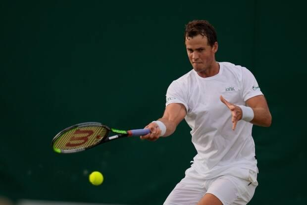 Canada's Vasek Pospisil plays a return to Frances Tiafoe of the U.S. during the men's singles second round match on the Wimbledon Tennis Championships in London in June. (Kirsty Wigglesworth/The Associated Press - image credit)