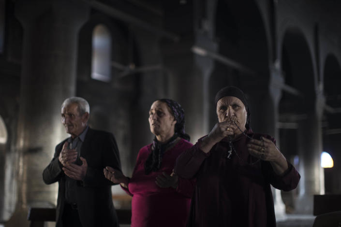 FILE - In this Nov. 12, 2016 file photo, Iraqi Christians pray at the Church of the Immaculate Conception, damaged by Islamic State fighters during their occupation of Qaraqosh, east of Mosul, Iraq. Iraq was estimated to have more than 1 million Christians before the 2003 U.S.-led invasion that toppled dictator Saddam Hussein. Now, church officials estimate only few hundred remain within Iraq borders. The rest are scattered across the globe, resettling in far-flung places like Australia, Canada and Sweden as well as neighboring countries. (AP Photo/Felipe Dana, File)
