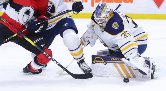 Buffalo Sabres goaltender Linus Ullmark (35) keeps his eyes on the puck as Sabres defenseman Brandon Montour holds off Ottawa Senators center Chris Tierney during the second period of an NHL hockey game Monday, Dec. 23, 2019, in Ottawa, Ontario. (Sean Kilpatrick/The Canadian Press via AP)