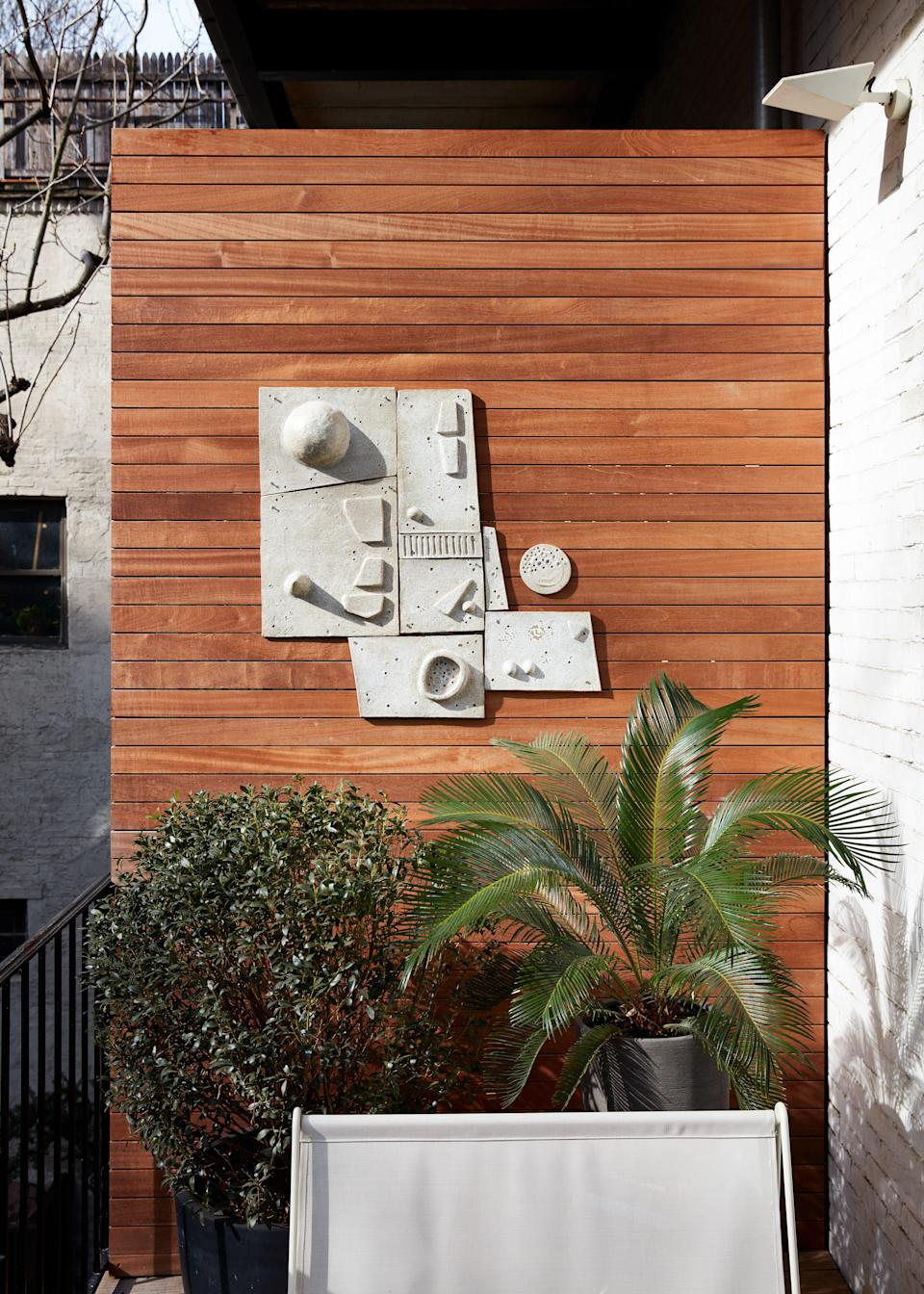 "Of his south-facing sun-drenched balcony, Otero says, ""It's pretty much my favorite place in my apartment! It really is an oasis—very calm."" He designed the deck and side wall panels in mahogany. One of his pieces hangs on a side panel."