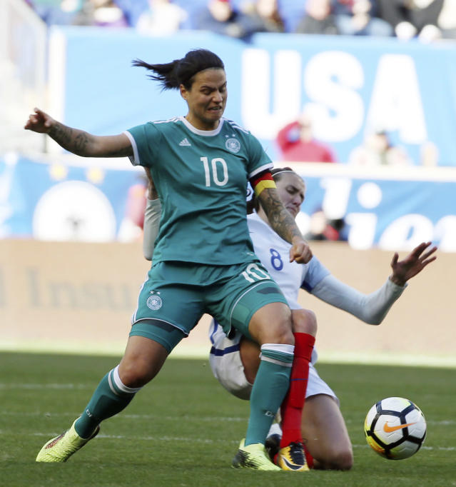 FILE - In this March 4, 2018, file photo, Germany midfielder Dzsenifer Marozsan (10) is tackled by England midfielder Jill Scott (8) during the first half of a SheBelieves Cup women's soccer match, in Harrison, N.J. The Women's World Cup kicks off Friday, June 7, 2019, in Paris. Marozsan is the inspirational story of the World Cup, having returned to the game after a pulmonary embolism kept her sidelined for several months last year. (AP Photo/Steve Luciano, File)