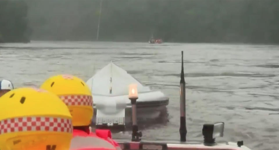An emergency boat capsized in swollen flood waters while rescuing a family of four.