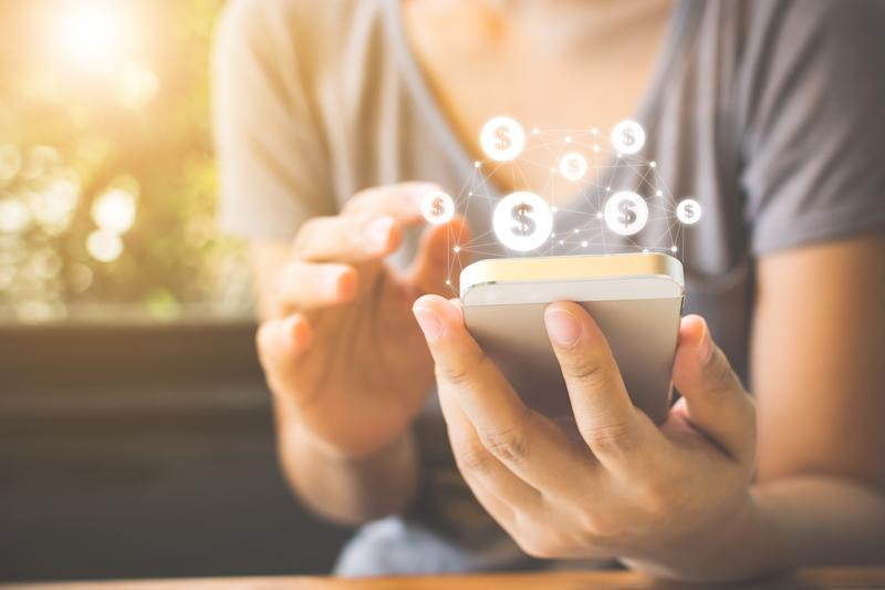 A person holding a smartphone with dollar signs appearing above the phone.