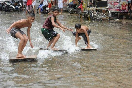 <p>Children use plywood to surf in a flooded street in Navotas in suburban Manila in August. Typhoon Bopha, expected to hit the southern island of Mindanao overnight, is the strongest typhoon to hit the Philippines this year.</p>