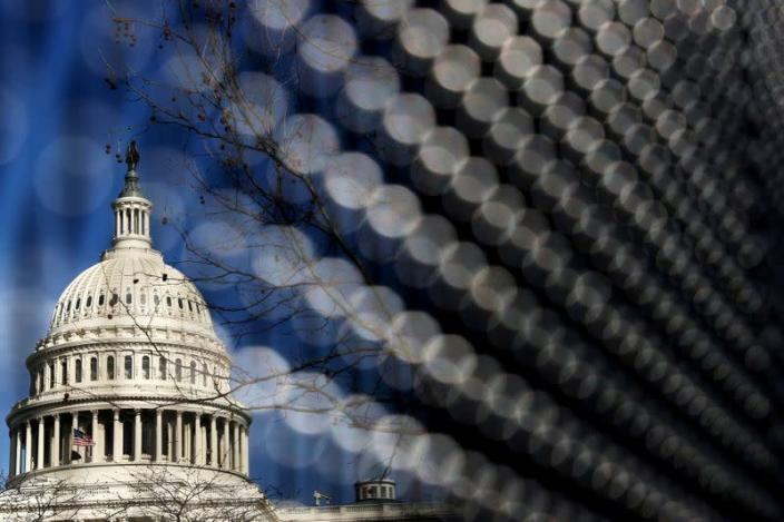 FILE PHOTO: Light catches the security fence around the U.S. Capitol, erected in the wake of the January 6th attack but now scheduled to start being removed, in Washington