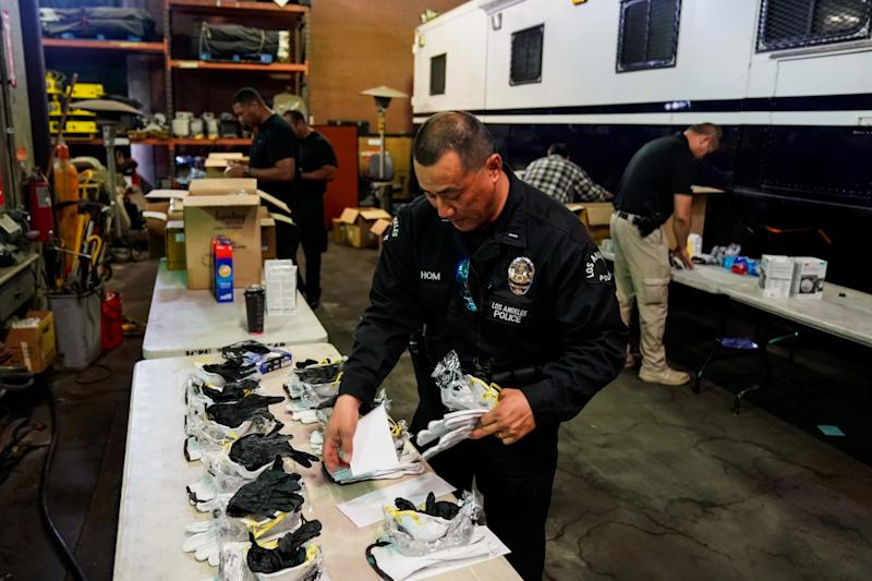 LAPD Lt. Jay Hom assembles coronavirus kits consisting of an N95 mask, goggles, leather gloves and rubber gloves. The kits are going out to about 7,000 officers who work in the field.