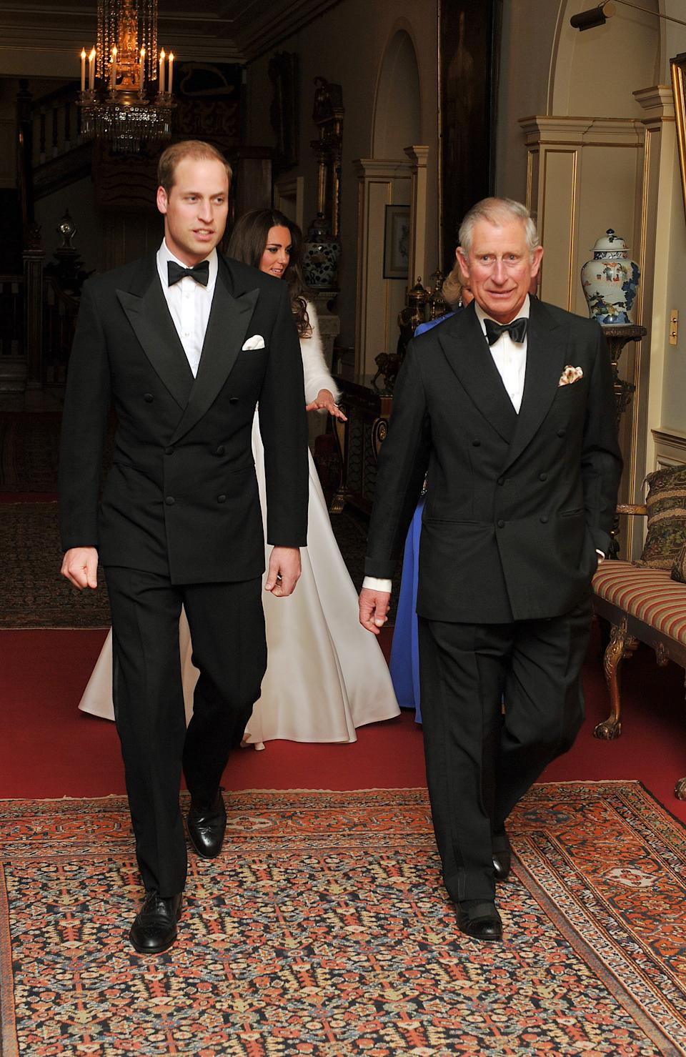 The Prince of Wales walks with his son Prince William followed by the Duchess of Cambridge and the Duchess of Cornwall, as they leave Clarence House to travel to Buckingham Palace for a dinner and party, this evening.