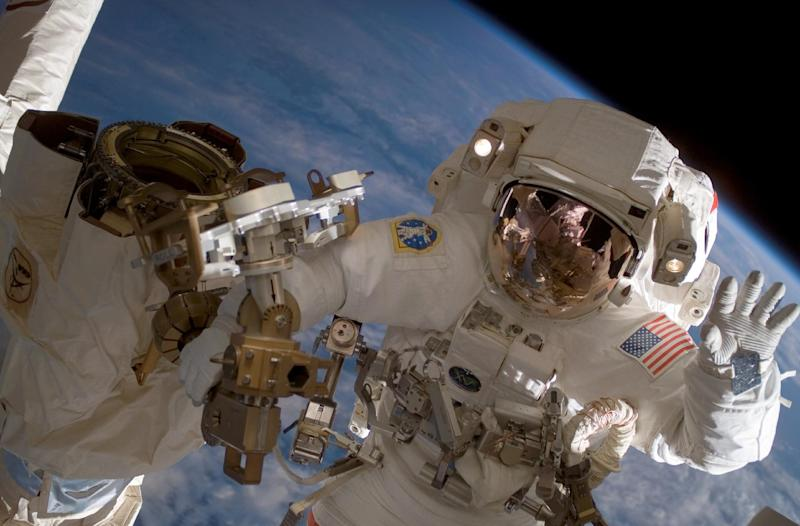 This July 2007 image provided by NASA shows astronaut Clay Anderson waving during a spacewalk outside the International Space Station. Astronauts traveling to and from Mars would be bombarded with as much cosmic radiation as they'd get from a full-body CT scan about once a week for a year, researchers reported Thursday, June 30, 2013. NASA aims to send a crew to orbit the red planet by the mid-2030s. (AP Photo/NASA)