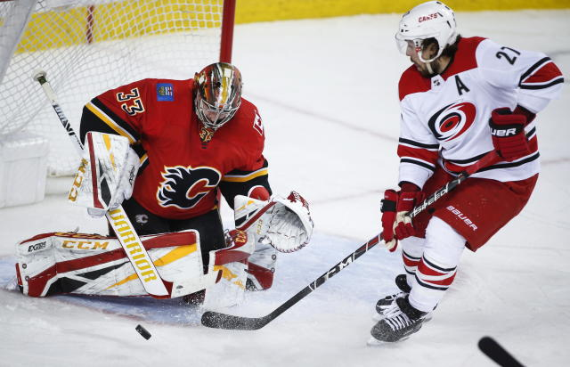 Carolina Hurricanes' Justin Faulk, right, has his shot deflected by Calgary Flames goalie David Rittich, of the Czech Republic, during second period NHL hockey action in Calgary, Tuesday, Jan. 22, 2019. (Jeff McIntosh/The Canadian Press via AP)
