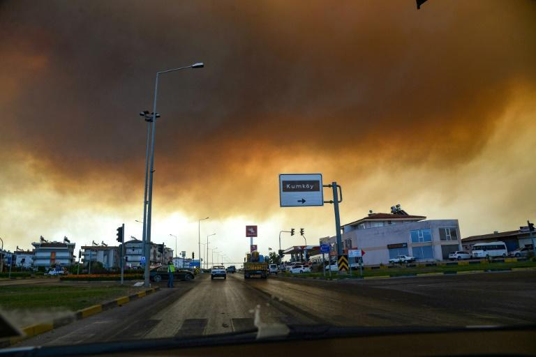 Heavy clouds of smoke rise from a massive forest fire which engulfed a Mediterranean resort region on Turkey's southern coast near the town of Manavgat, on July 29, 2021
