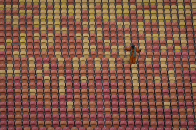 A worker is seen on the stands of the Arena da Amazonia soccer stadium in Manaus, Brazil, Tuesday, May 20, 2014. Arena da Amazonia will host matches of the 2014 World Cup in Brazil. (AP Photo/Felipe Dana)