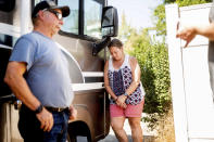 Kimberly Price leans against a donated motorhome she received with boyfriend John Hunter, left, on Sunday, Sept. 5, 2021, in Quincy, Calif. Hunter, who lost his home and business to the Dixie Fire, plans to live in the RV in Greenville. (AP Photo/Noah Berger)