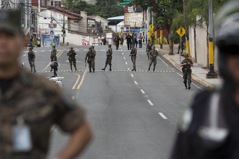 Soldiers stand guard close to the presidential house during a protest by supporters of Free Party presidential candidate Xiomara Castro in Tegucigalpa, Honduras, Monday, Nov. 25, 2013. The two top presidential candidates continued to claim victory Monday in a hotly contested presidential race, as Hondurans awaited final results. (AP Photo/Moises Castillo)