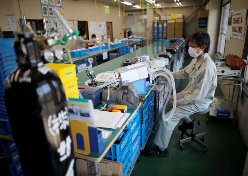 Employees of Sanko Manufacturing Co. are seen at the assemble line of the company's ventilators at the factory in Saitama