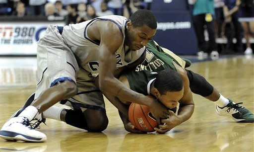 Georgetown's Jason Clark, left, and South Florida's Anthony Collins fight for control of the ball during first half of anir NCAA college basketball game, Saturday, Feb. 4, 2012, in Washington. Georgetown won 75-45. (AP Photo/Richard Lipski)