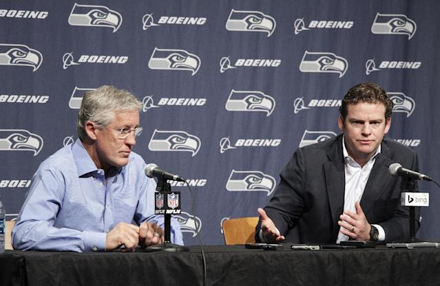 Seattle Seahawks NFL football head coach Pete Carroll, left, and Seattle Seahawks general manager John Schneider, right, talk to the media during a news conference Friday, April 4, 2014, in Renton, Wash. The Seahawks have locked up coach Carroll with a three-year contract extension after he led the franchise to its first Super Bowl title. (AP Photo/Marcus R. Donner)