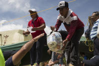 <p>Volunteers receive emergency supplies donated by Mexico City residents in San Gregorio Atlapulco, Mexico, Friday, Sept. 22, 2017. Mexican officials are promising to keep up the search for survivors as rescue operations stretch into a fourth day following Tuesday's major earthquake that devastated Mexico City and nearby states. (AP Photo/Moises Castillo) </p>