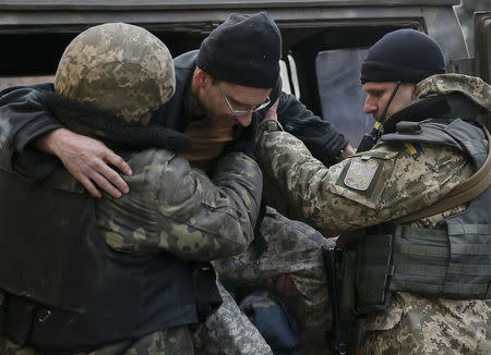 Ukrainian servicemen carry a wounded comrade into a hospital in Artemivsk February 8, 2015.  REUTERS/Gleb Garanich