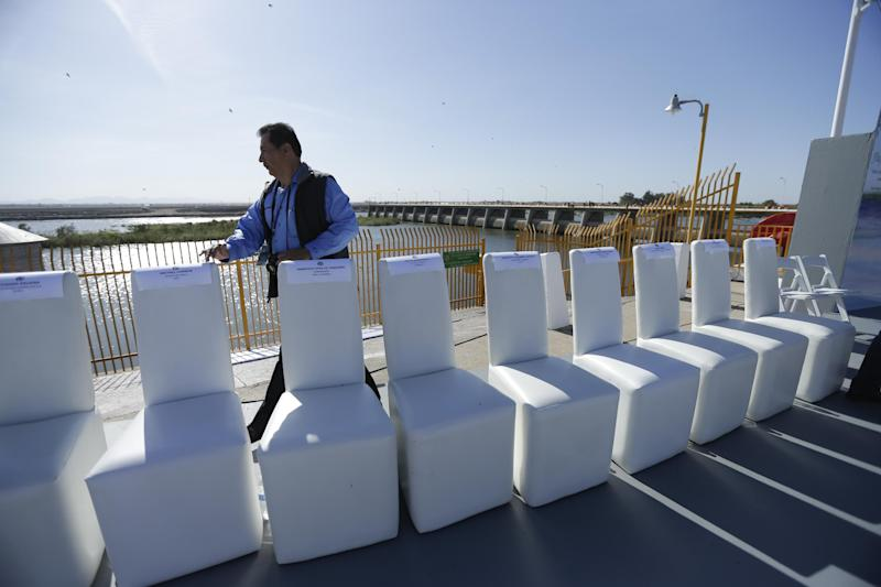 A Mexican official counts the chairs for visiting dignitaries shortly before a ceremony to mark the climax of a Colorado River water pulse event Thursday, March 27, 2014, Los Algodones, Mexico. Colorado River water has begun pouring over a barren delta near the U.S.-Mexico border, the result of a landmark bi-national agreement being celebrated Thursday. (AP Photo/Gregory Bull)