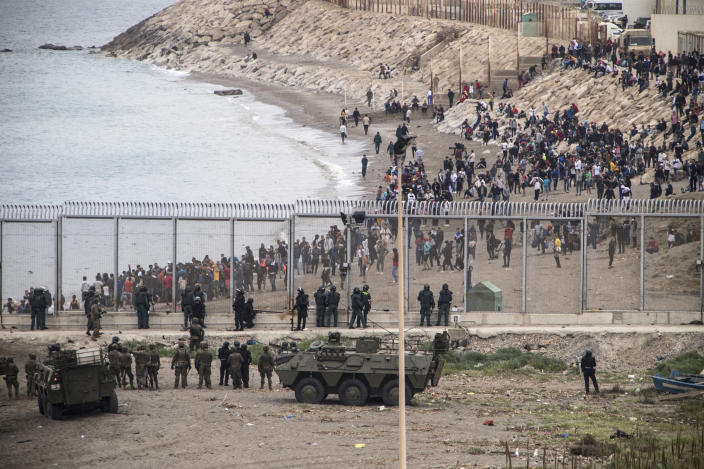 Spanish Army take positions at the border of Morocco and Spain, at the Spanish enclave of Ceuta, on Tuesday, May 18, 2021. Ceuta, a Spanish city of 85,000 in northern Africa, faces a humanitarian crisis after thousands of Moroccans took advantage of relaxed border control in their country to swim or paddle in inflatable boats into European soil. Around 6,000 people had crossed by Tuesday morning since the first arrivals began in the early hours of Monday, including 1,500 who are presumed to be teenagers. (AP Photo/Javier Fergo)