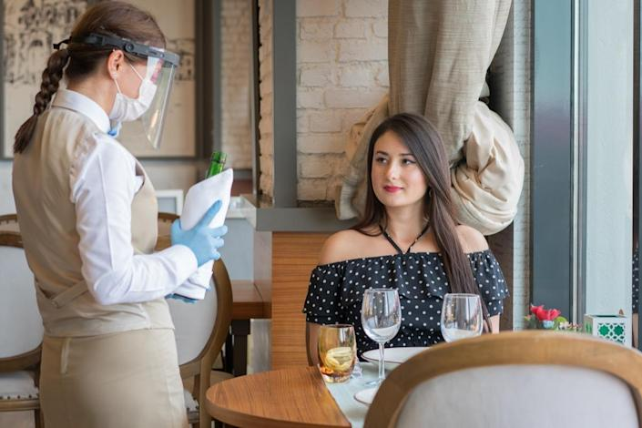 Waiter serving red wine in a luxury restaurant with face mask Covid 19.