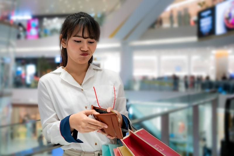 Portrait of unhappy stressed beautiful person looking in open wallet with shocked expression while holding color shopping bags at mall. Young model spent too much money during shopping time