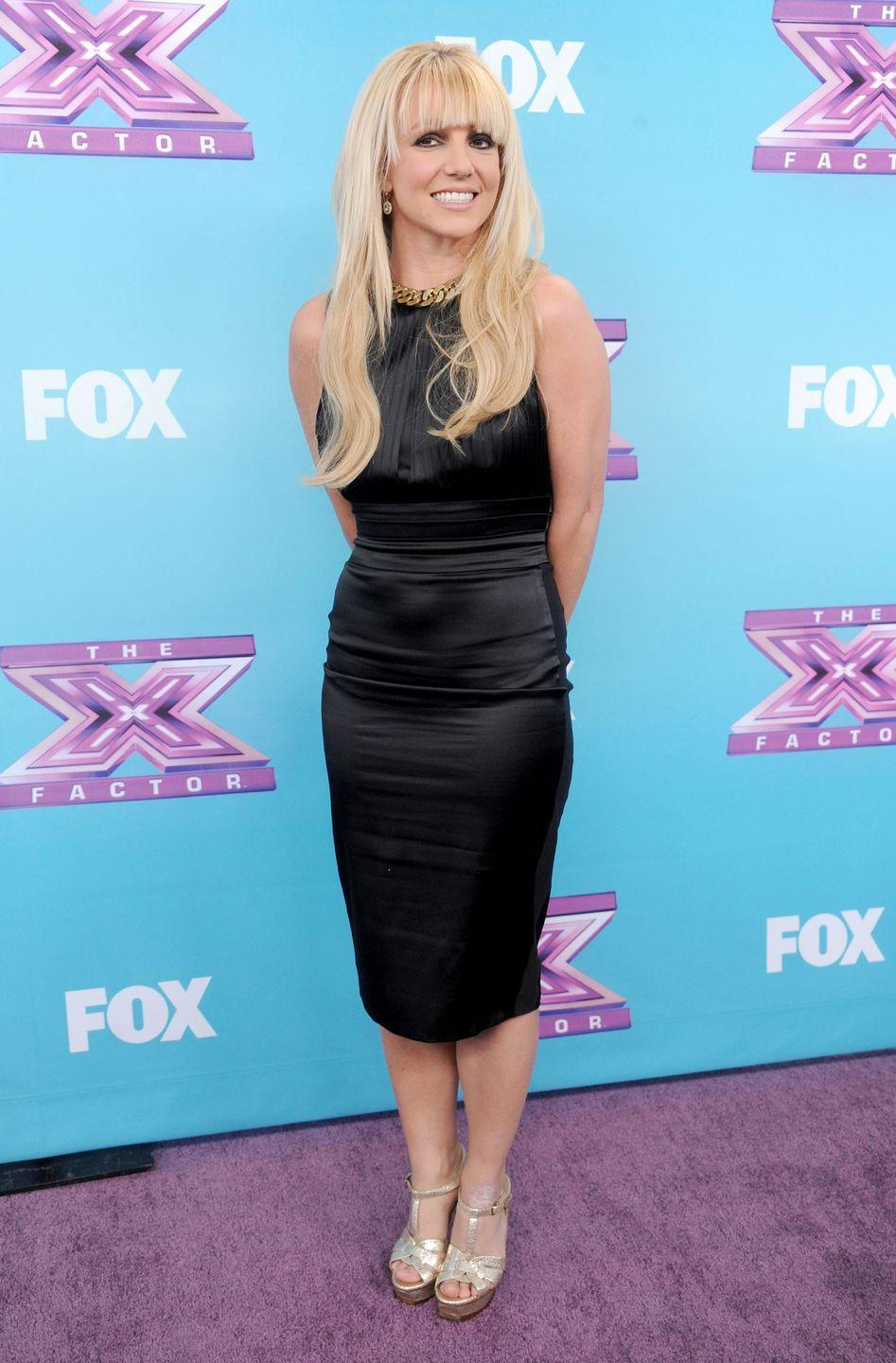 <p>Brit rocks some new bangs at <em>The X Factor</em> season finale with a black sheath dress and metallic heels. </p>