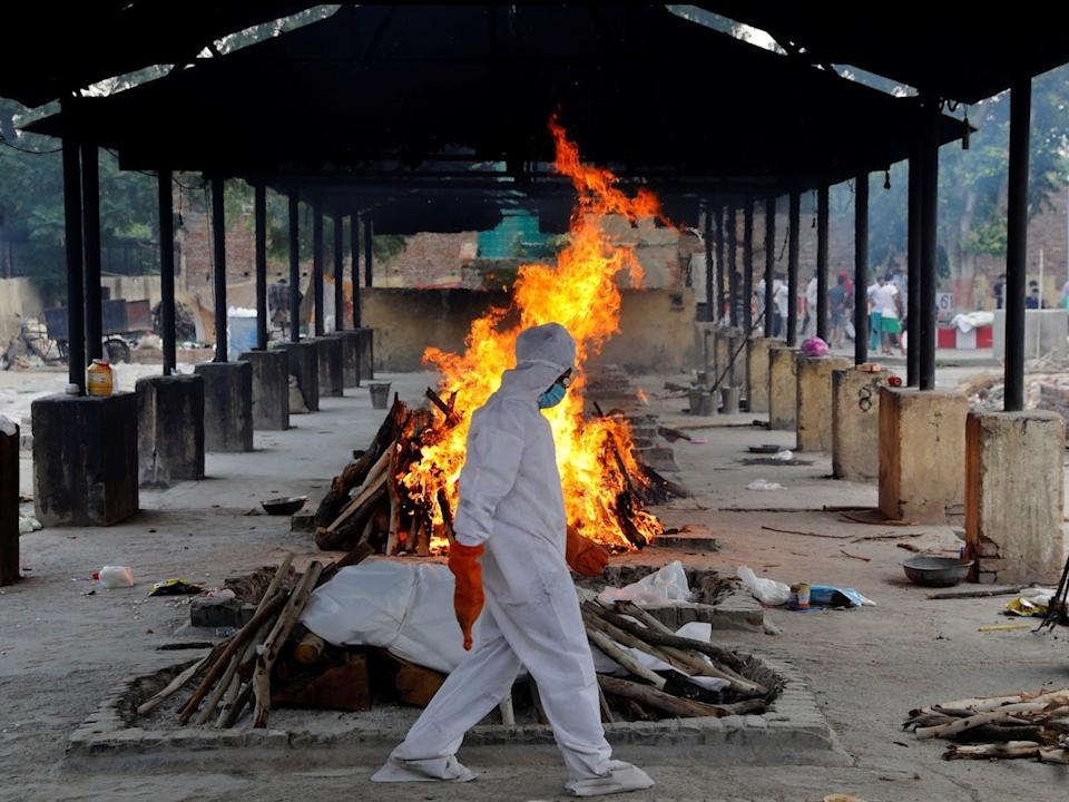 A priest walks in front of the body of a person who died of the coronavirus disease, as he collects woods to make a funeral pyre at a crematorium in New Delhi, India, on July 3, 2020.