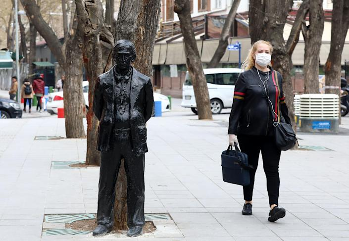 A woman wears a mask in Ankara, Turkey, on 30 March. (Getty Images)