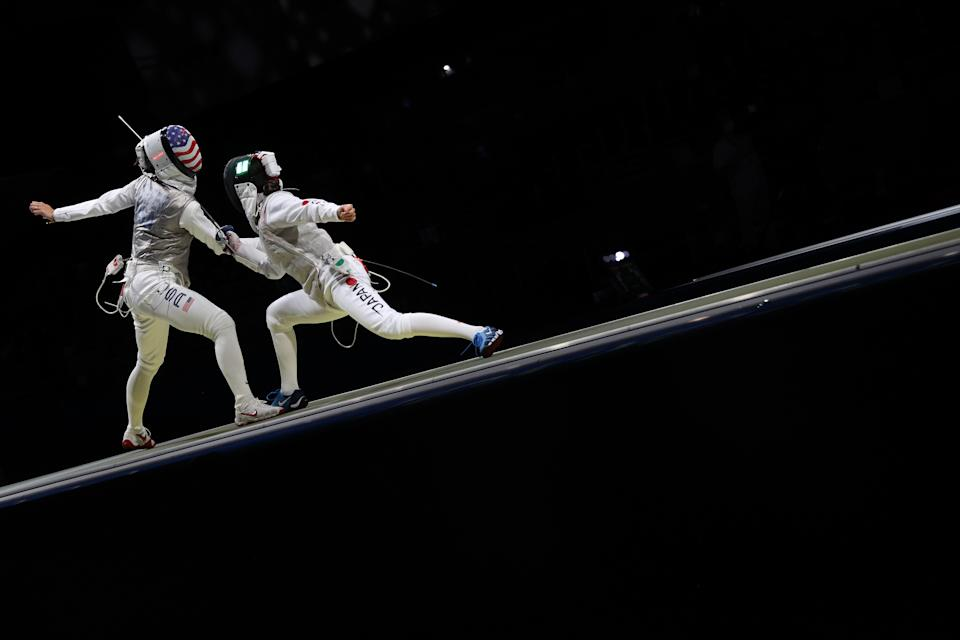 <p>Lee Kiefer of Team United States, left, competes against Rio Azuma of Team Japan in Women's Foil Team Quarterfinal on day six of the Tokyo 2020 Olympic Games at Makuhari Messe Hall on July 29, 2021 in Chiba, Japan. (Photo by Elsa/Getty Images)</p>