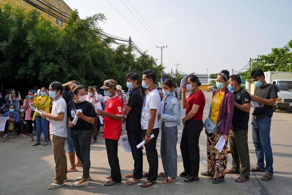 Garment factory workers and staff wait to receive the Sinovac vaccine.