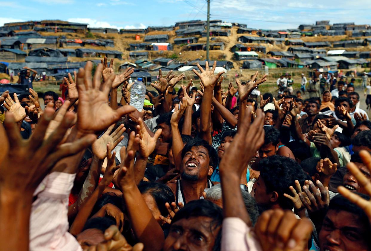 Rohingya refugees stretch their hands to receive aid distributed by local organizations at Balukhali makeshift refugee camp in Cox's Bazar, Bangladesh, on Sept. 14, 2017.