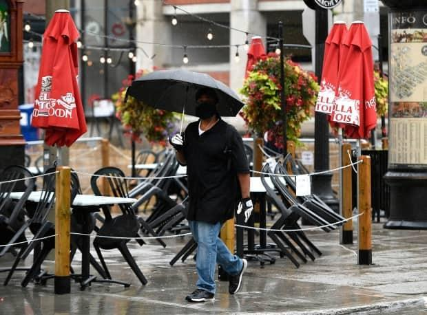 A person passes beside a Byward Market restaurant's empty patio as rain falls on Sunday, Sept. 13, 2020.  (Justin Tang/Canadian Press - image credit)