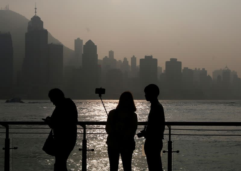 FILE PHOTO: A couple takes a selfie during sunset on a waterfront facing the financial Central district in Hong Kong