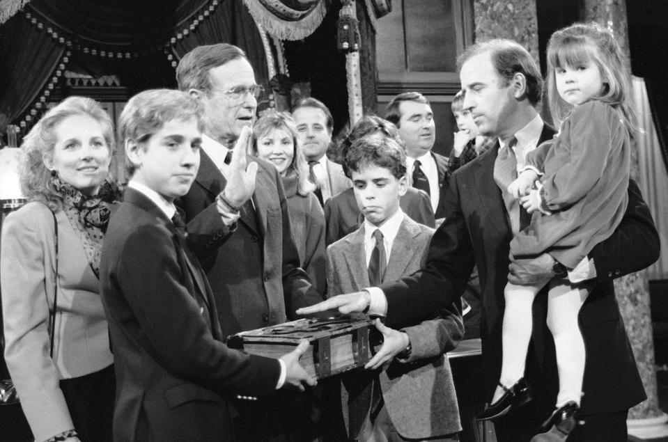 Sen. Joe Biden, D-Del., holds his daughter Ashley while taking a mock oath of office from Vice President George Bush during a ceremony on Capitol Hill, in Washington, Jan. 3, 1985. Biden's sons Beau and Hunter hold the bible during the ceremony. (AP Photo/Lana Harris)