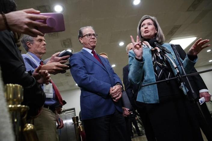 Sen. Mike Braun, R-Ind., left, listens as Sen. Joni Ernst, R-Iowa, speaks to the media during a break in the impeachment trial of President Donald Trump on charges of abuse of power and obstruction of Congress, Friday, Jan. 24, 2020, on Capitol Hill in Washington. (AP Photo/Jacquelyn Martin)