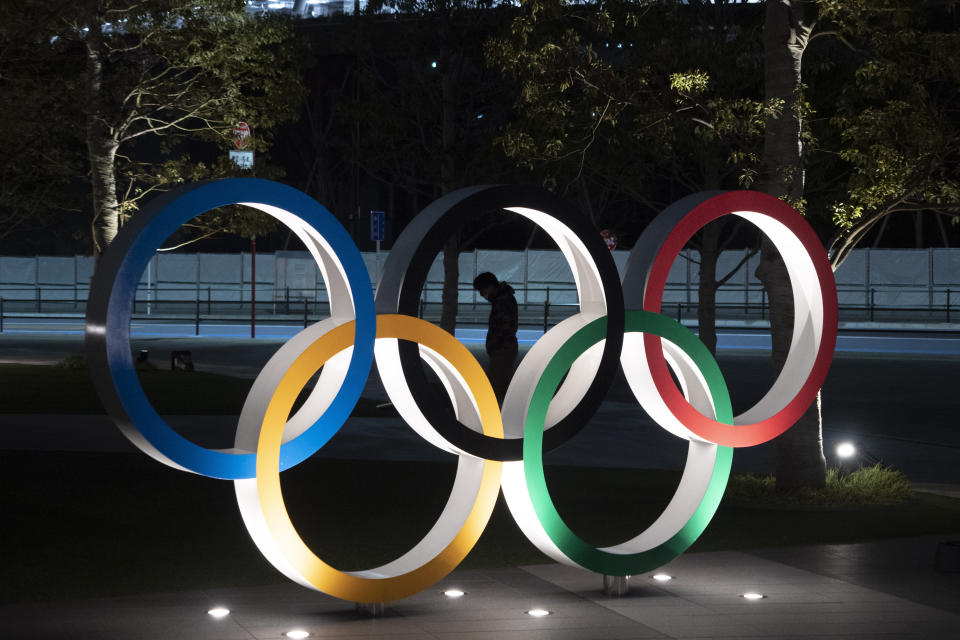 "A man is seen through the Olympic rings in front of the New National Stadium in Tokyo, Tuesday, March 24, 2020. IOC President Thomas Bach has agreed ""100%"" to a proposal of postponing the Tokyo Olympics for about one year until 2021 because of the coronavirus outbreak, Japanese Prime Minister Shinzo Abe said Tuesday. (AP Photo/Jae C. Hong)"