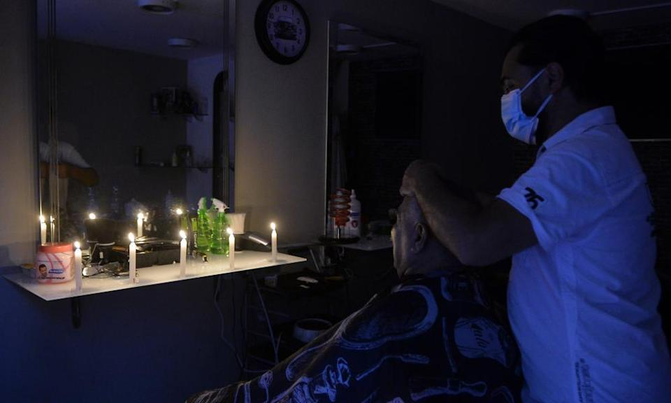 A man gets his hair cut in the dark at a barber shop in Beirut during a power cut caused by fuel shortages.
