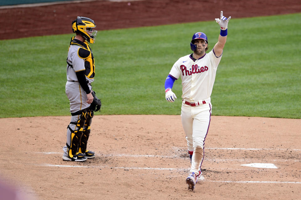 Philadelphia Phillies' Bryce Harper, right, reacts after hitting solo home run off Pittsburgh Pirates starting pitcher Wil Crowe (not shown) during the third inning of a baseball game, Saturday, Sept. 25, 2021, in Philadelphia. (AP Photo/Derik Hamilton)