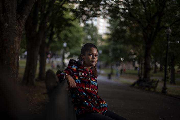 """Alyssa Harris, 18, a member of the Mashpee Wampanoag Tribe, sits for a portrait in a park in Boston, Friday, Oct. 2, 2020. """"I just feel like this is the four hundredth anniversary of colonization. And I mean, why why would I celebrate that? Like, celebrating getting my culture, language, land taken away? Four hundred years ago was the start of all that,"""" said Harris who also works as a historical educator. """"But then on top of that, since there's this anniversary, I've been given the opportunity to use my voice, whereas in prior years I've never been asked to. I definitely think people will listen more, especially because there's the Black Lives Matter movement, which is already influencing people to learn more about history."""" (AP Photo/David Goldman)"""