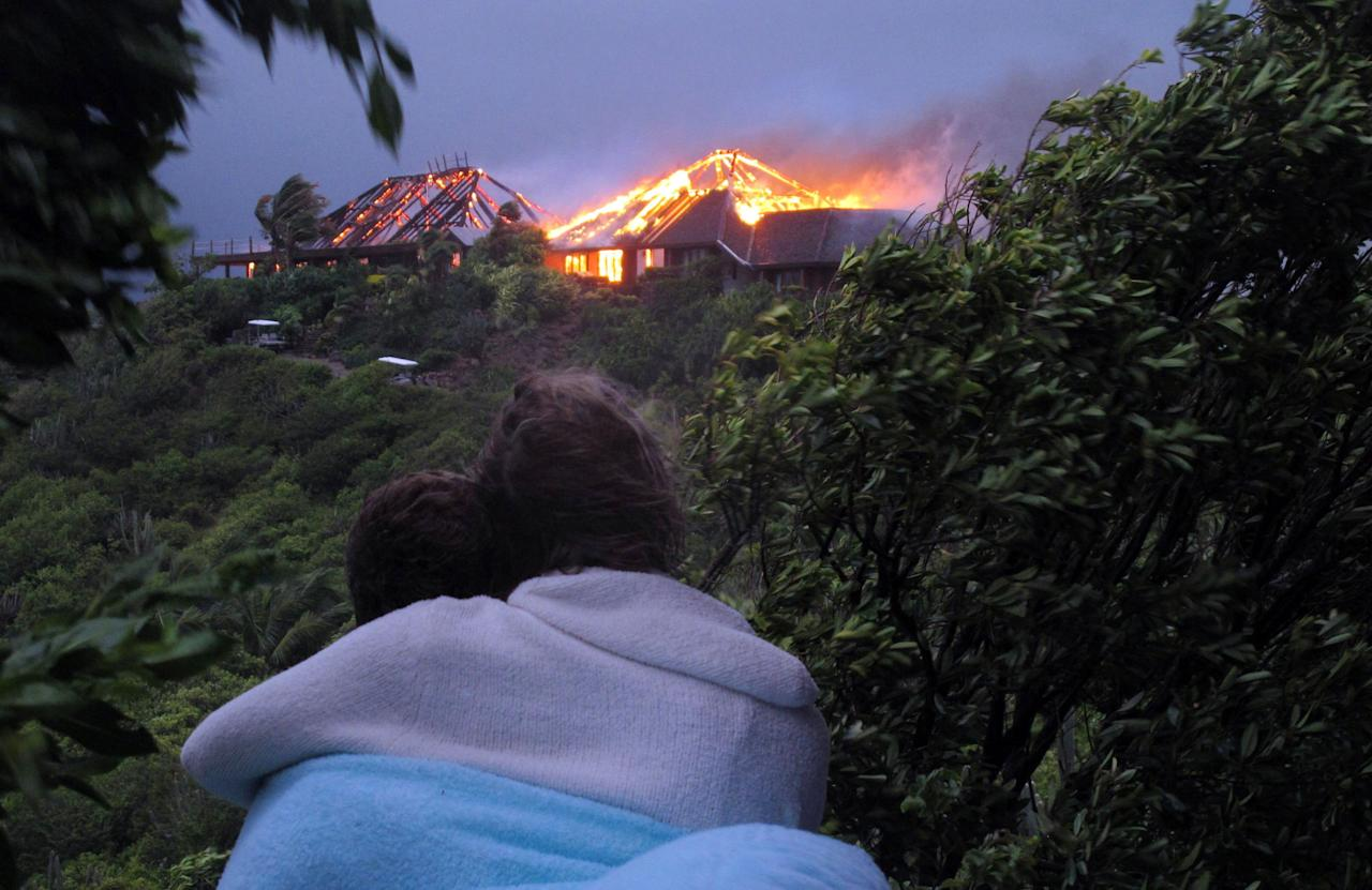 In this image issued Monday Aug. 22, 2011 by Virgin Limited Edition shows an unidentified couple looking towards British entrepreneur's Sir Richard Branson's luxury home, on Necker Island, in the Caribbean, as it burns . Guests including Academy Award-winning actress Kate Winslet escaped uninjured when fire destroyed Richard Branson's Caribbean home during a tropical storm Monday, said the British businessman. The Virgin Group boss said about 20 people, including Winslet and her children, were staying in the eight-bedroom Great House on Necker, his private isle in the British Virgin Islands. (AP Photo/Virgin Limited Edition/PA) UNITED KINGDOM OUT NO SALES NO ARCHIVE EDITORIAL USE ONLY